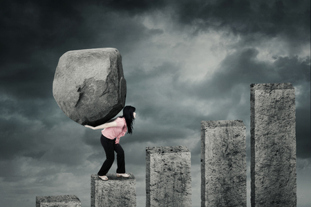 Weibliche Unternehmer klettern eine finanzielle Diagramm bei der Durchführung eines großen Stein auf dem Rücken mit bewölktem Himmel