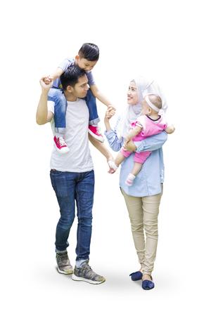 Twee moslimouders en hun kinderen lopen in de studio tijdens een gesprek met elkaar, geïsoleerd op een witte achtergrond Stockfoto