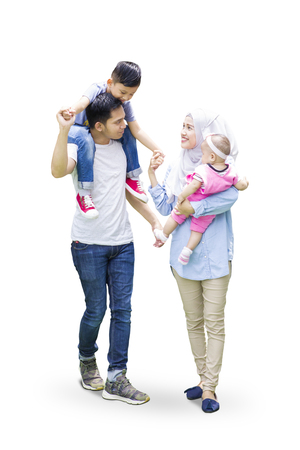 Two muslim parents and and their kids walking in the studio while talking to each other, isolated on white background Stock fotó