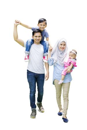 Pełna długość muzułmańskiej rodziny spaceru w studio, podczas gdy ojciec niosący syna na ramieniu