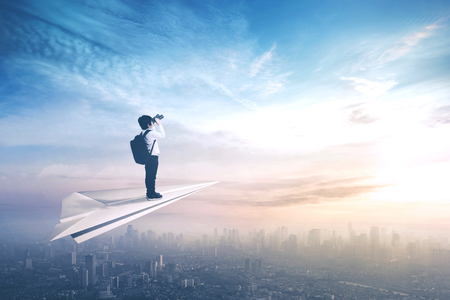 Picture of a little boy standing on a paper aeroplane while flying above a city and looking through a binoculars