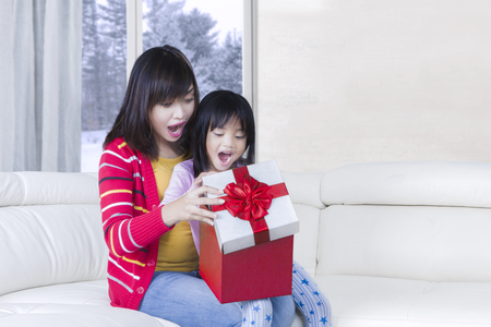 red sofa: Portrait of little daughter and mother feeling surprised while opening gift box with winter background on the window