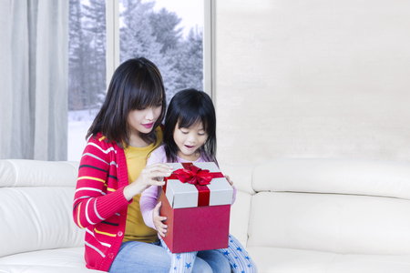 asian children: Young mother and cute daughter opening gift box together while sitting on the sofa with winter background on the window Stock Photo