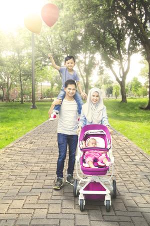 ベビーカーと風船を保持している息子に赤ちゃんと一緒に公園を歩いて美しいイスラム教徒の家族の肖像画
