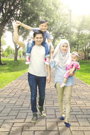 手を繋いでいる間公園の方法で幸せなイスラム教徒家族の歩行、カメラで笑顔