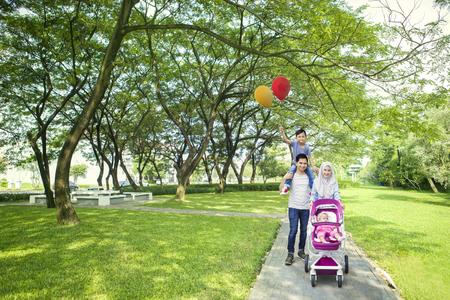 カメラの笑顔しながら公園で子どもと一緒に楽しんでイスラム教徒の両親の肖像画 写真素材