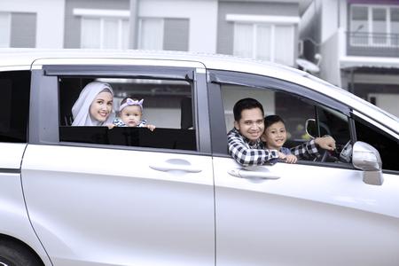 Gelukkige muslim familie glimlachen bij de auto raam terwijl kijkend naar de camera, buitenshuis geschoten