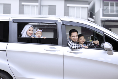 Happy muslim family smiling at the car window while looking at the camera, shot outdoors