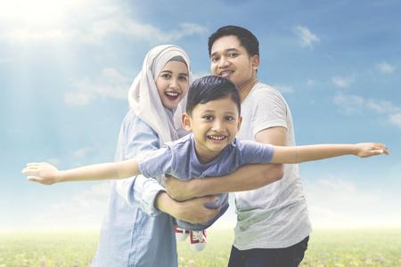 牧草地でカメラに笑顔の息子と一緒に遊んでイスラム教徒の両親のイメージ