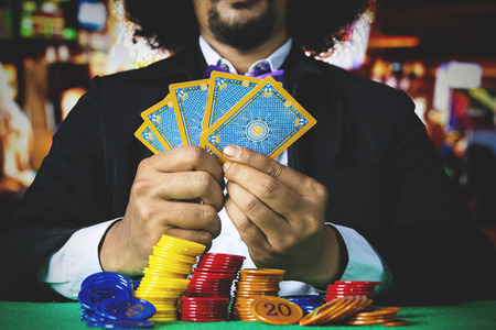 Businessman gambling with poker cards and stack of chip on the table in the casino