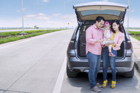 Happy family standing behind the car while looking digital tablet on the road