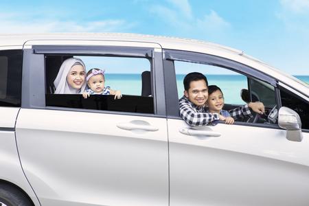백그라운드에서 해변보기와 함께 카메라를 웃고있는 동안 차에 앉아 젊은 가족의 이미지 스톡 콘텐츠