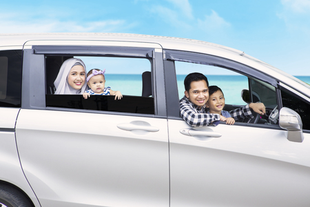 Image of young family sitting in the car while smiling at the camera with beach view in the background