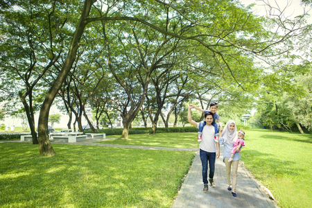 Picture of a young Asian family smiling at the camera while spending time in the park