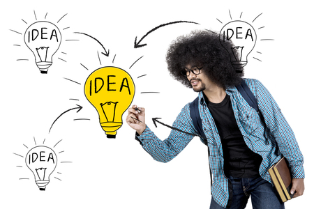 Afro man drawing light bulb on virtual screen while holding book, isolated on white background