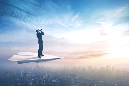 Picture of a young businessman standing on a paper plane while flying above a city and looking through a binoculars photo