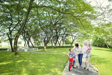 Afbeelding van schattige jongen leert om te fietsen met zijn gezin tijdens het wandelen samen in het park Stockfoto