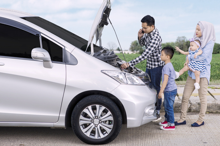 Image of Asian father speaking on a mobile phone while standing front of broken car with his family on side of road