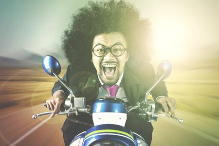 Portret van gelukkige afrozakenman die een motorfiets met een dwaze gezichtsuitdrukking berijdt