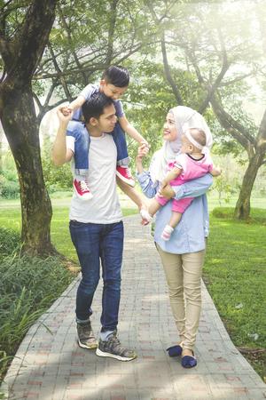 一个年轻的亚洲家庭在公园里散步时看起来很快乐