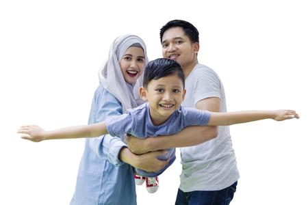 Photo d'un mignon petit garçon volant sur ses mains les parents tout en regardant la caméra dans le studio Banque d'images - 76984082