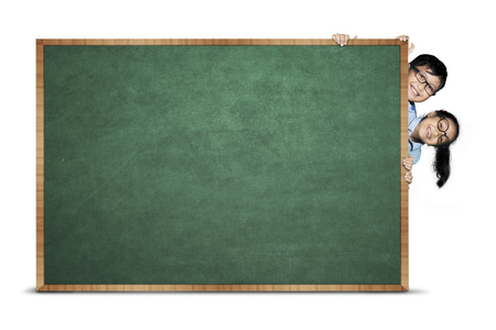 Image of primary students hiding behind blank chalkboard, isolated on white background Stock Photo