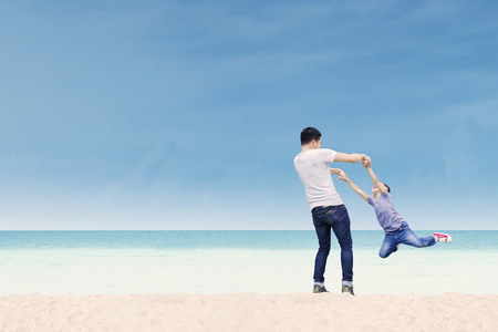 Portrait of a cheerful young father playing and spinning his son on the beach Stock Photo