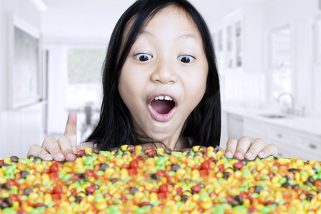 Photo of a surprised little girl looking at colorful candies on the table, shot in the kitchen at home Stock Photo