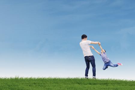 Het portret van jonge vader kijkt gelukkig terwijl het spelen met zijn zoon in de weide