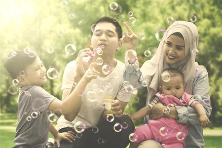 Beeld van het vrolijke Moslimfamilie spelen met zeepbels en het hurken in het park Stockfoto