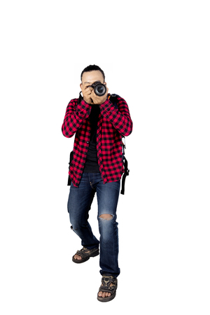 Portrait of young male hiker using a digital camera to taking a picture while standing in the studio