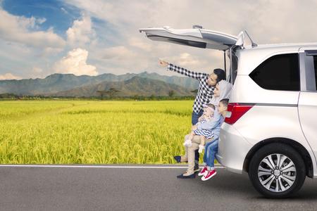 Beeld van Aziatische familiezitting achter een auto terwijl het bekijken iets met bergmening op de achtergrond Stockfoto