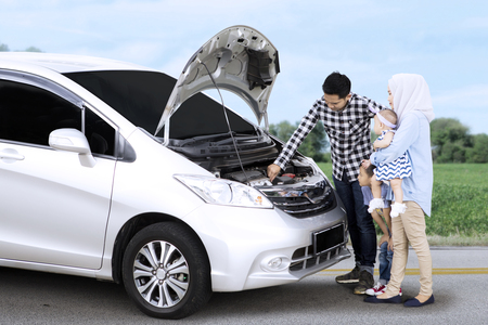 Image of young father checking a broken car while standing with his family on the road side