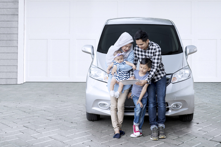 Picture of Muslim family sitting in front of a car while using a digital tablet in the house garage Stock Photo