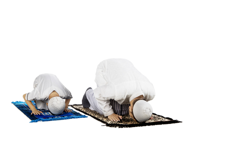 Picture of a devout family posing prostration while praying to the Allah, isolated on white background Stock Photo