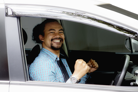 Photo of cheerful Afro man smiling happy inside his new car while wearing casual clothes Stock fotó
