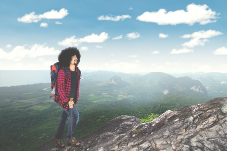 Portrait of a male hiker with curly hair, climbing a mountain while holding a stick and carrying backpack