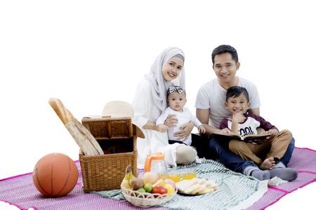 asian foods: Happy Asian muslim family smiling at the camera while picnicking together with a picnic basket and foods on the mat, isolated on white background