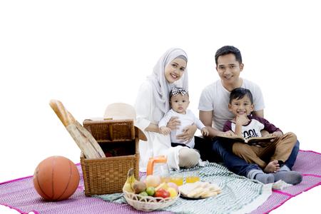 Heureuse famille musulmane asiatique souriante à la caméra tout en pique-nique avec un panier de pique-nique et des aliments sur le tapis, isolé sur fond blanc Banque d'images - 77317672
