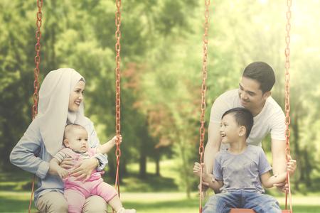 2 つの陽気なイスラム教徒の家族と公園でブランコに乗って一緒に楽しみを持つ子供たちの肖像画