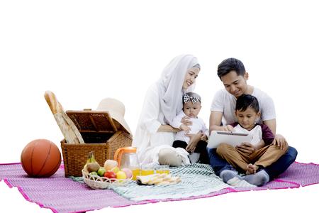 Gelukkige moslimfamilie die samen en een digitale die tablet met picknickmand op mat picnicking gebruiken, op witte achtergrond wordt geïsoleerd Stockfoto