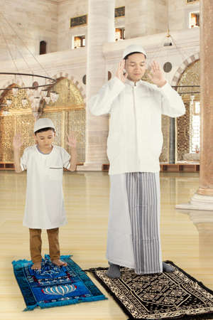 prayer rug: Full length a young muslim father teaching his son for praying in the mosque Stock Photo