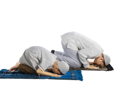 Portrait of Asian family wearing Islamic clothes while posing prostration, isolated on white background Stock Photo