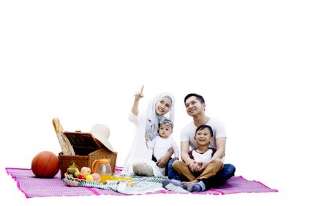 快乐的穆斯林家庭一起野餐,一起坐在垫子上,看着一些东西,孤立在白色的背景