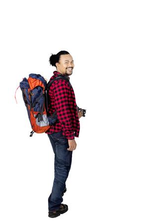 スタジオのカメラで笑顔のバックパックとデジタル カメラを運ぶ若い男性ハイカーの肖像画 写真素材