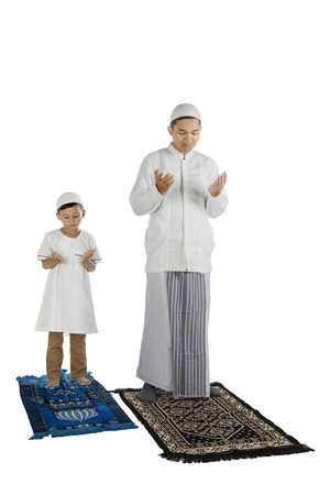 Portrait of devout family praying to the Allah while standing in the studio