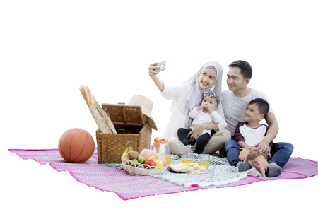 Happy muslim family taking selfie photo while picnicking together with a picnic basket and foods on mat Stock Photo