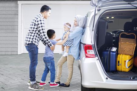 집 차고에서 차 근처에 서있는 동안 여행 할 준비가되어있는 아이들과 무슬림 부모님의 그림