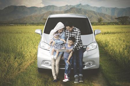 논 앞에 디지털 태블릿을 사용하는 동안 자동차 앞에 앉아있는 회교도 가족 이미지 스톡 콘텐츠
