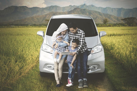Image of Muslim family sitting in front of a car while using a digital tablet in the rice field
